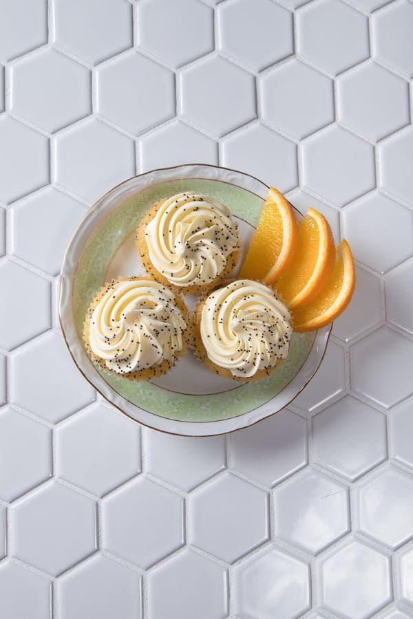 Arancia e Poppy Seed Cupcakes deliziose con i segmenti arancio fotografia stock libera da diritti