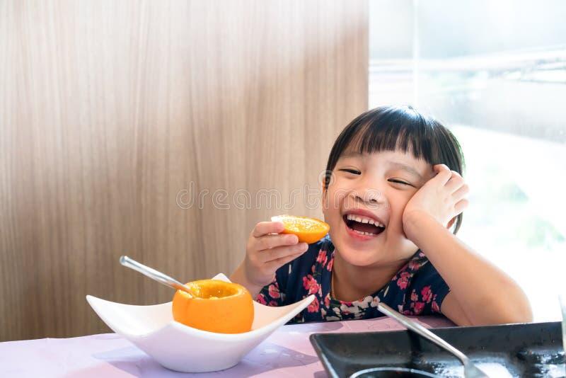 Arancia fresca del bambino di cibo felice asiatico della ragazza immagini stock