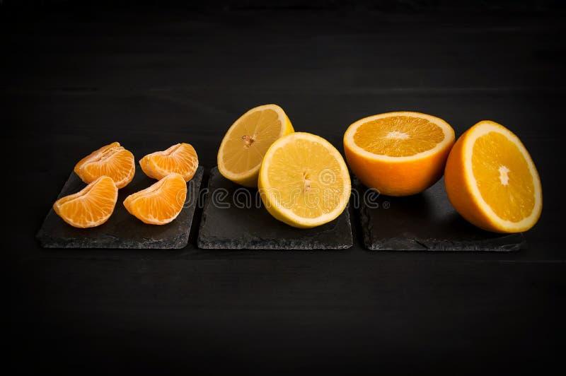 Arancia, limone, mandarino, su un fondo nero immagine stock