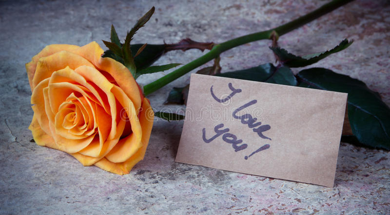 Arancia rosa e nota ti amo sulla carta del mestiere fotografia stock