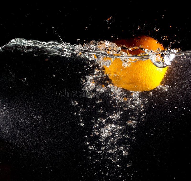 Arancia sotto acqua su un fondo nero fotografia stock libera da diritti