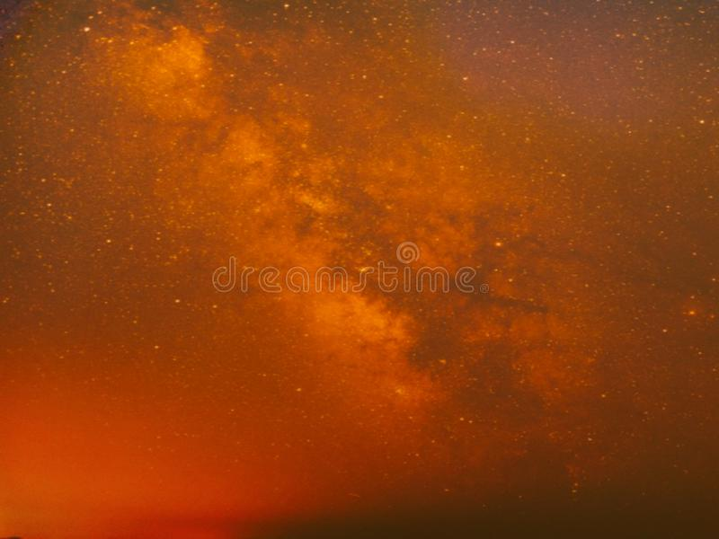 Arancia sul cielo e sulla galassia scura fotografia stock libera da diritti