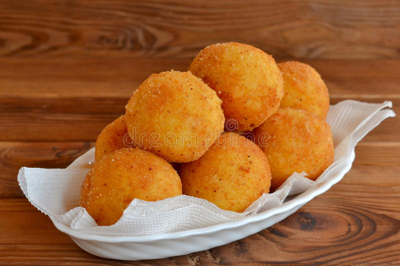 Arancini balls on a plate. Fried rice balls recipe. Rice cutlets. Brown wooden background stock images