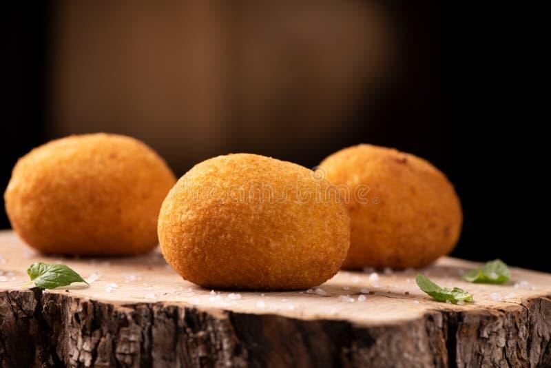 Arancini - italienische Reisbälle, die mit Brotkrumen beschichtet werden stockfoto