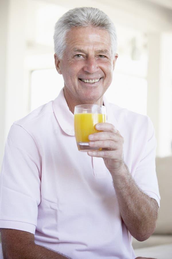 arancio centrale bevente invecchiato dell'uomo della spremuta fotografie stock libere da diritti