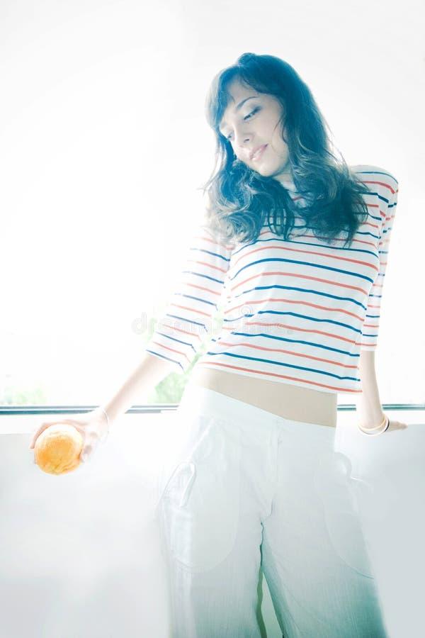 Arancio della holding della ragazza fotografia stock