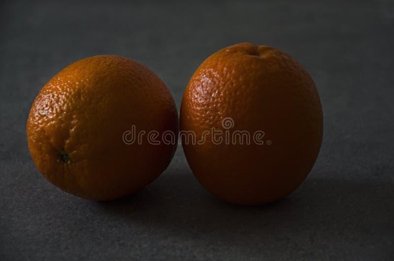 Arancio due succosi e le arance fresche sono sul ripiano del tavolo immagine stock libera da diritti