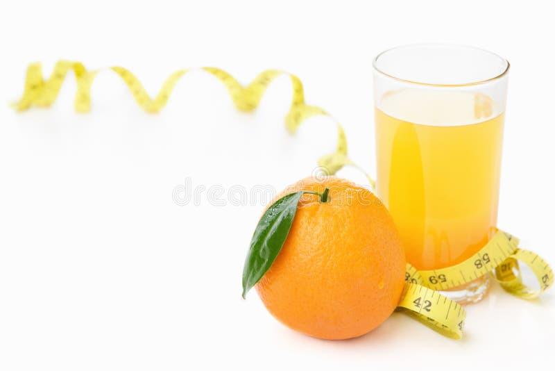 Arancio e spremuta con nastro adesivo di misurazione fotografia stock