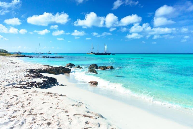 Arashi Wyrzucać na brzeg Aruba morza karaibskiego piaska skał kryształ - jasne turkus wody łodzie obraz stock