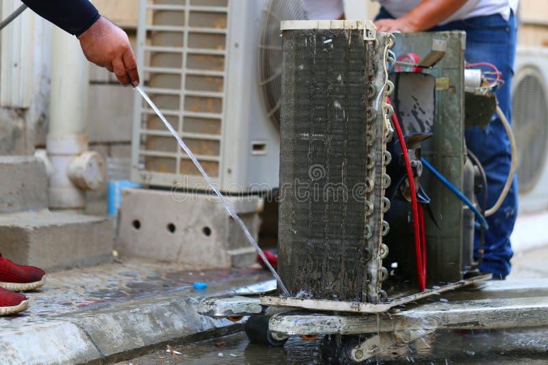 Arbeider aan het schoonmaken van rolkoeler van airconditioner door water voor schoon een stof op de muur in klantenhuis wanneer d stock afbeelding