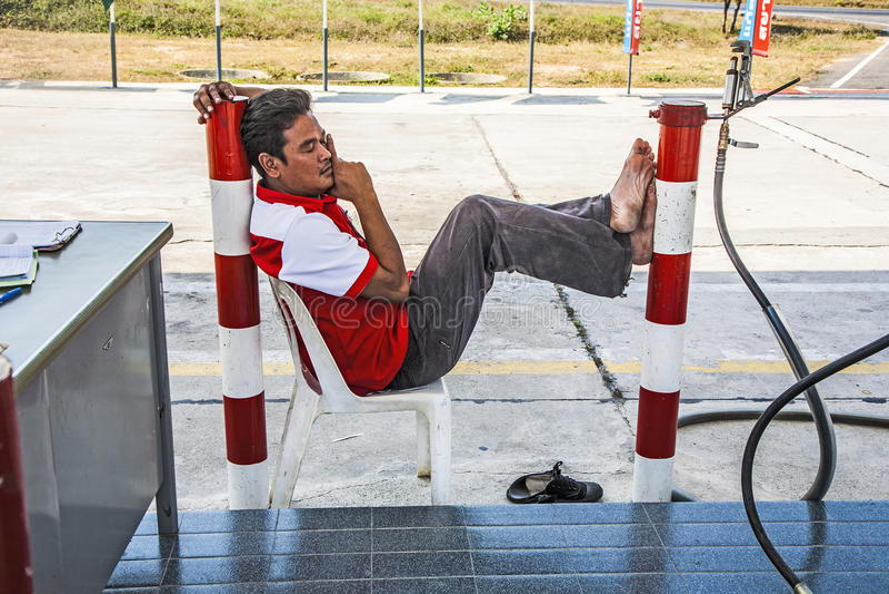 Arbeider bij de slaap van de benzinepost op een plastic stoel royalty-vrije stock afbeeldingen