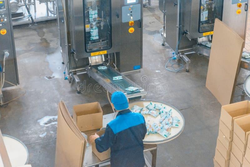 Arbeider bij de zuivelfabriek stock afbeelding