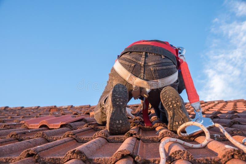 Arbeider bij het dak met veiligheidstoestel stock foto