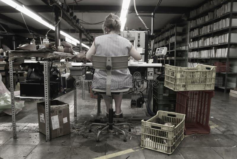 Arbeider bij met de hand gemaakt schoenmakenpakhuis stock foto's