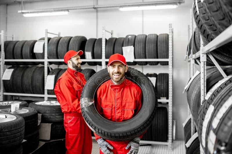 Arbeider die autoband in de opslag dragen royalty-vrije stock afbeeldingen