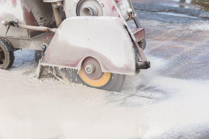 Arbeider die betonweg met het bladmachine van de diamantzaag snijden stock foto's