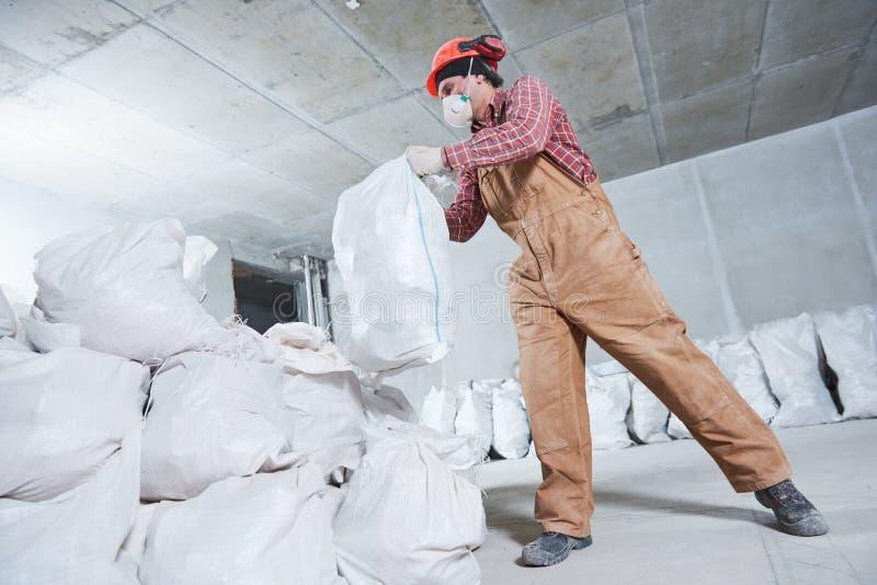 Arbeider die bouwafval in zak verzamelen royalty-vrije stock fotografie