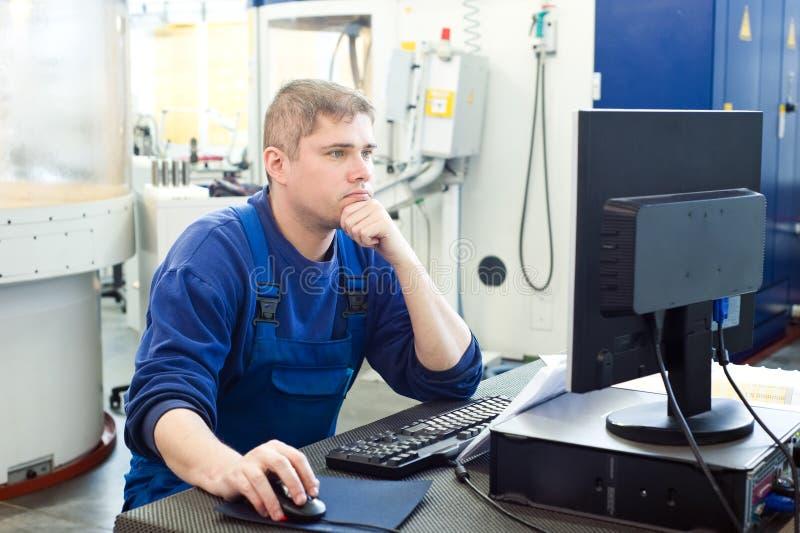 Arbeider die CNC machinecentrum in werking stelt stock fotografie