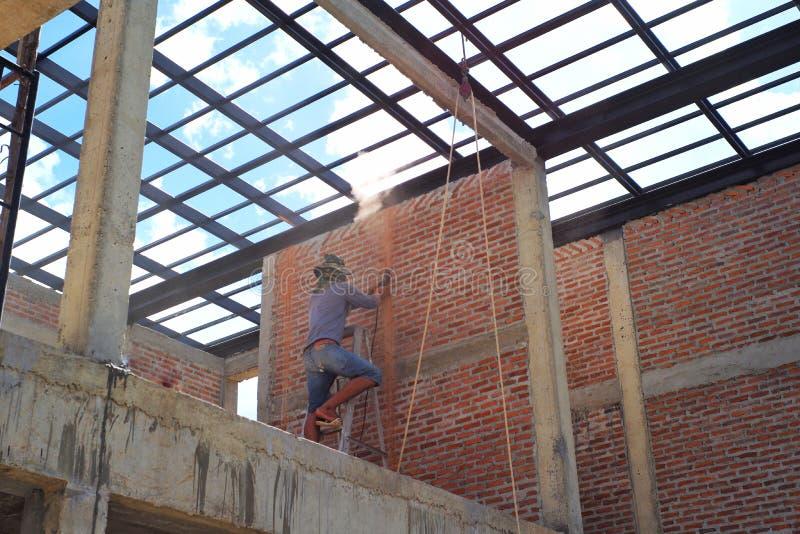 Arbeider die de bakstenen muur met de structuur van het staaldak en blauwe hemel op achtergrond snijden royalty-vrije stock fotografie