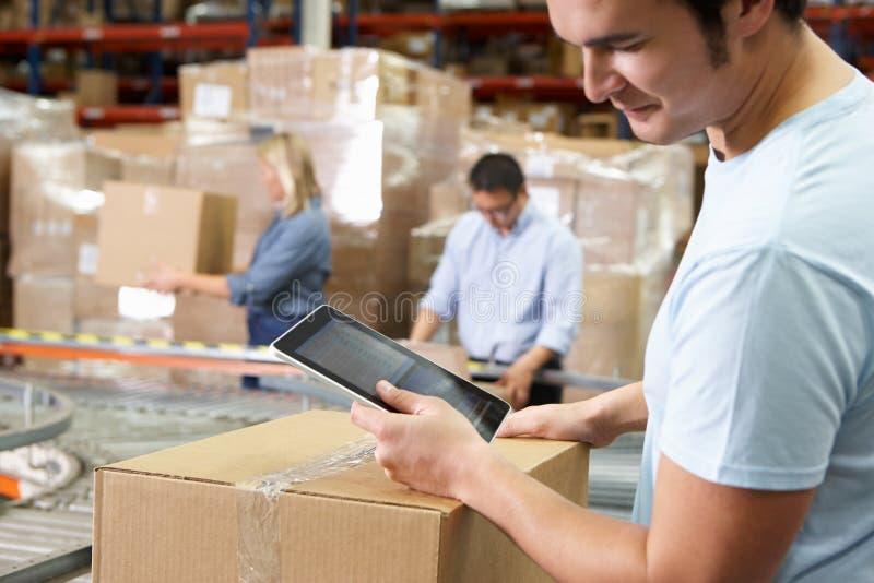 Arbeider die de Computer van de Tablet in het Pakhuis van de Distributie met behulp van royalty-vrije stock afbeeldingen