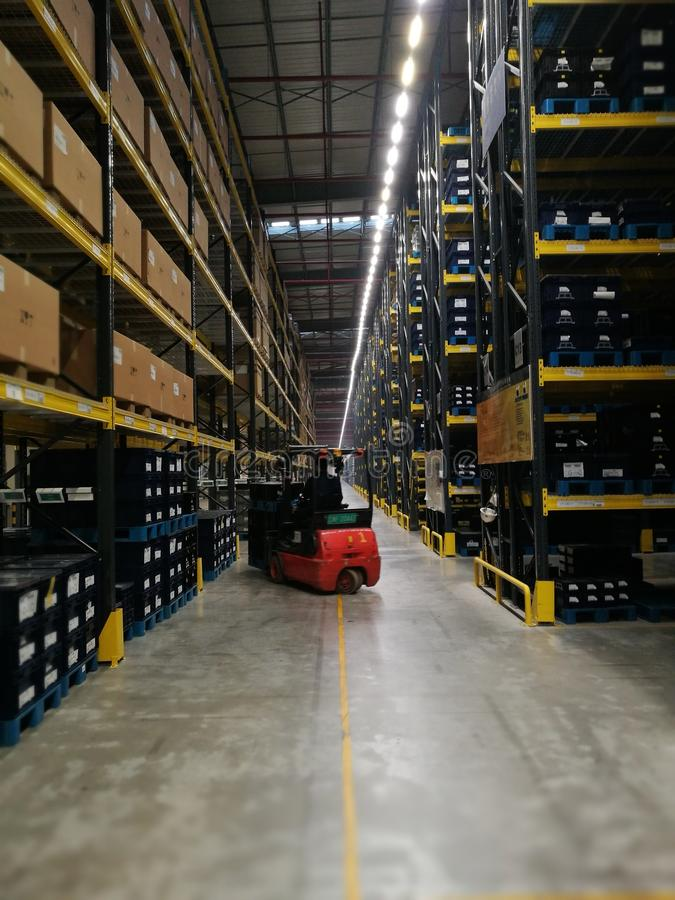 Arbeider die de goederen opheffen binnen aan de hoge plank met de autolift royalty-vrije stock foto's