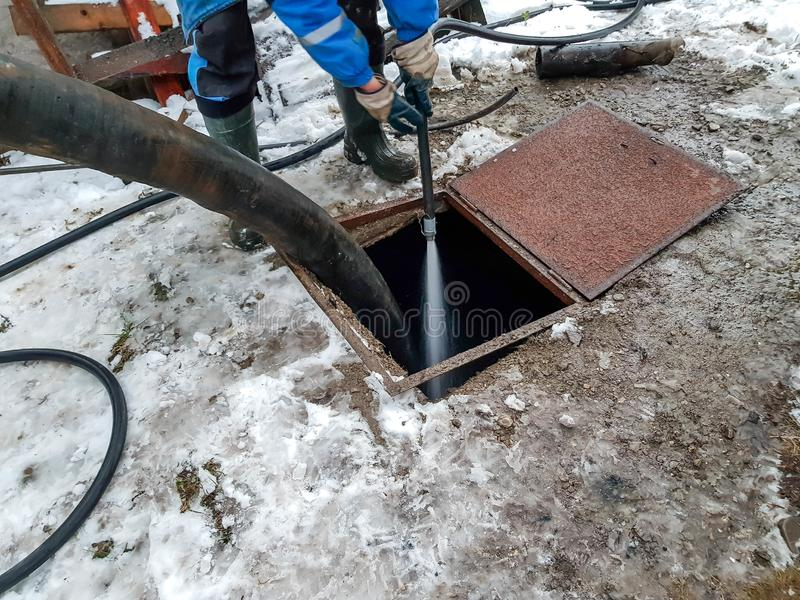 Arbeider die de sceptische put met water na het leegmaken schoonmaken door riolerings schonere machines royalty-vrije stock afbeelding