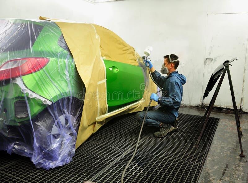 Arbeider die een auto schildert. stock foto