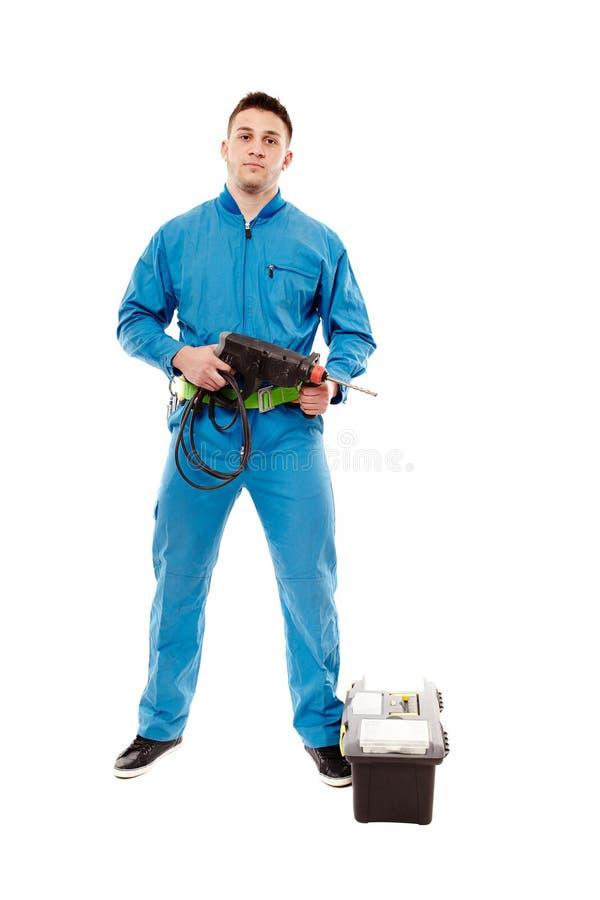 Arbeider die een boor houden dichtbij een hulpmiddeldoos stock foto's