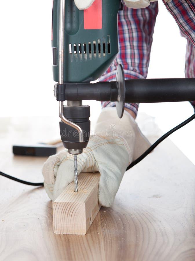 Arbeider die een gat in het hout boort royalty-vrije stock foto