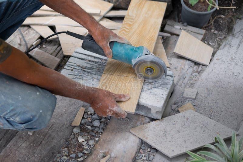Arbeider die een hand cirkelzaag gebruiken om een tegel te snijden stock fotografie
