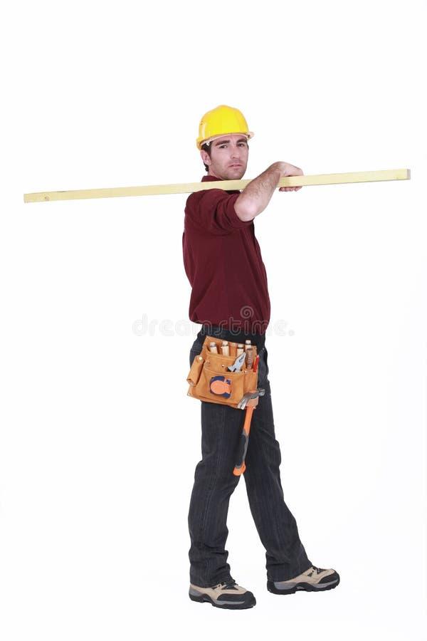 Arbeider die een plank dragen royalty-vrije stock afbeeldingen