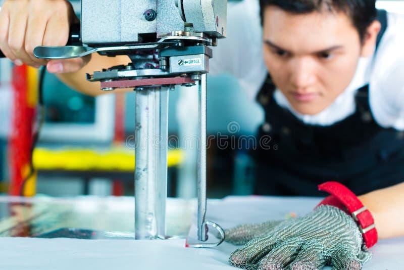 Arbeider die een machine in Chinese fabriek met behulp van stock fotografie