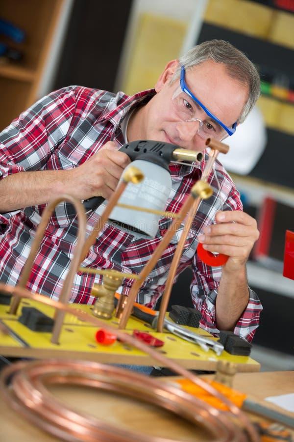 Arbeider die een soldeerlamp gebruiken royalty-vrije stock foto