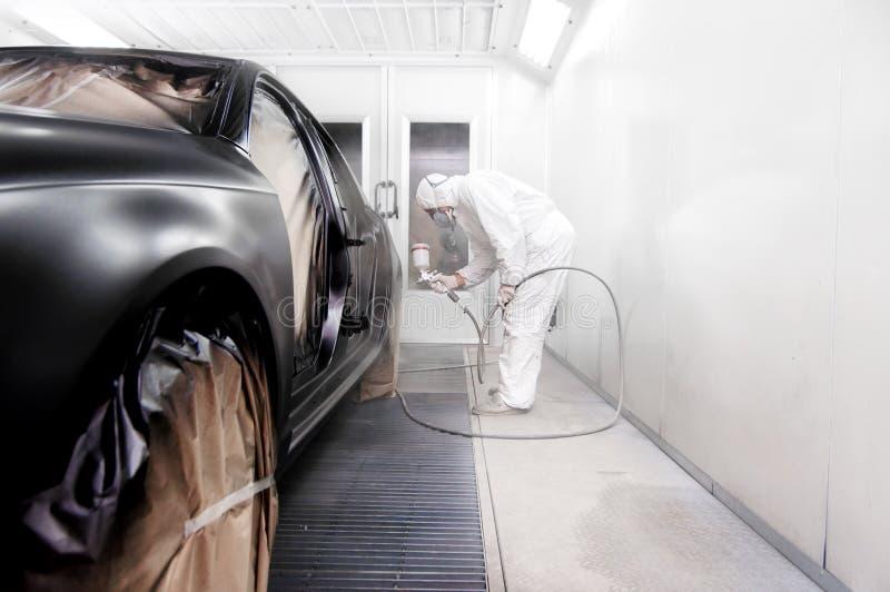 Arbeider die een zwarte auto in een speciale garage schilderen stock afbeelding