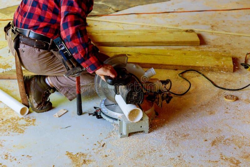 Arbeider die elektrische zaag gebruiken die pvc-pijp in bouw nieuwe commerciële bouw snijden stock fotografie