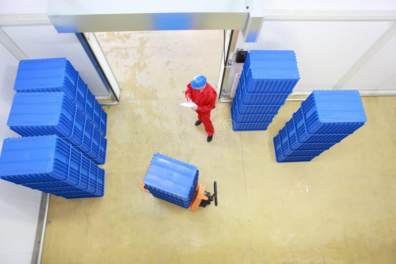 Arbeider die goederenlevering in pakhuis voorbereidt stock afbeeldingen