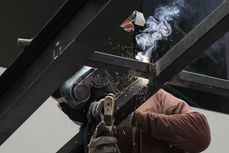 Arbeider die het staal lassen stock foto's