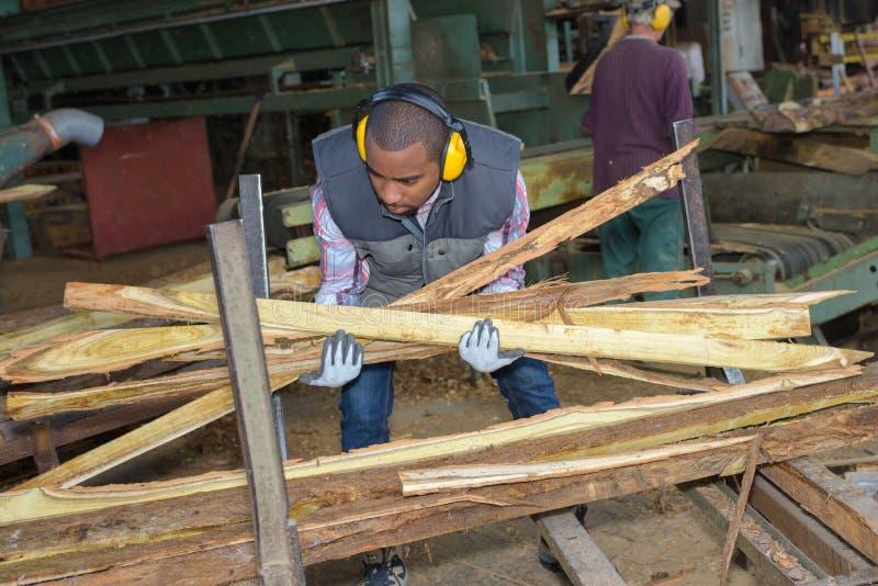 Arbeider die hout opnemen stock foto