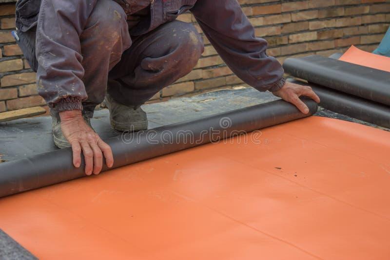 Arbeider die isolatiemateriaal voor kelderverdiepingsmuur 3 voorbereiden stock foto