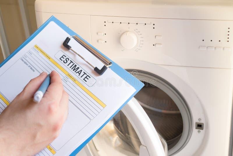 Arbeider die kosten voor gebroken wasmachine schatten stock foto