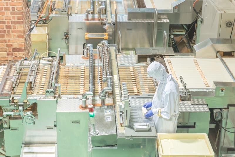 Arbeider die met machine in koekjesfabriek werken royalty-vrije stock foto