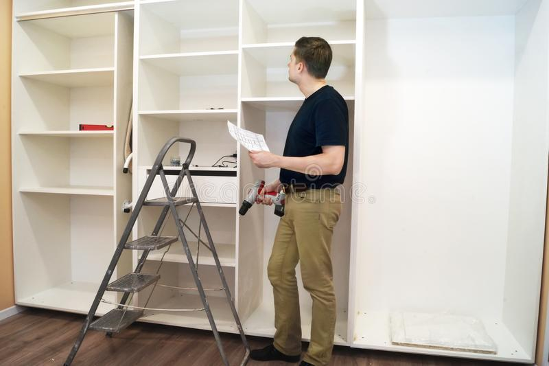 Arbeider die met schroevedraaier nieuw kabinet inspecteren stock foto's