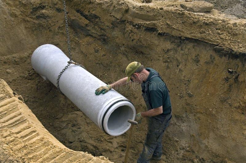 Arbeider die nieuwe rioolpijp in groef in de straat leggen stock foto