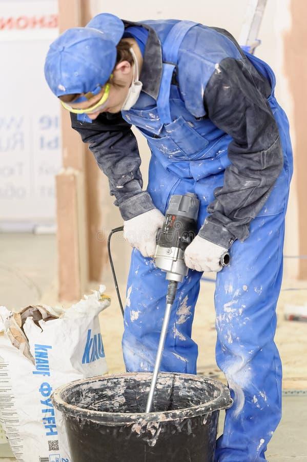 Arbeider die pleister mengen met een boor in een emmer stock foto's