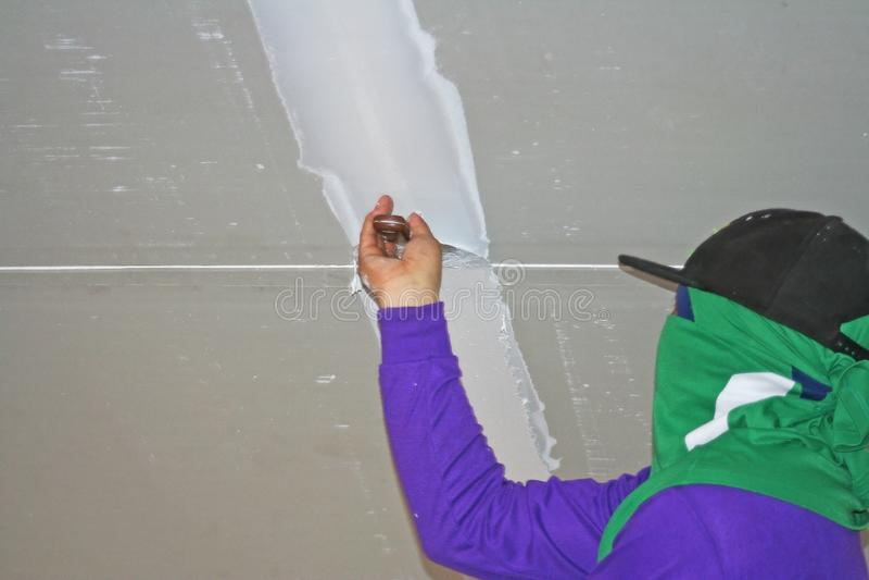 Arbeider die pleistergips op stopverfmes gebruiken bij plafond stock afbeelding
