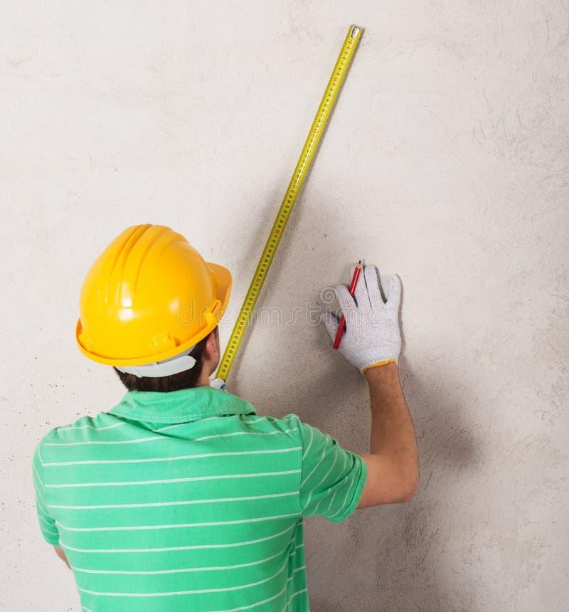 Arbeider die pleistermuur meten royalty-vrije stock foto