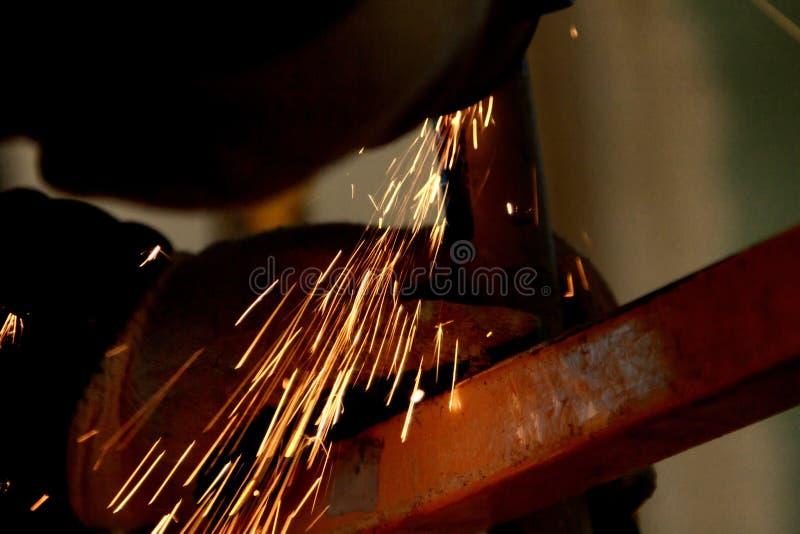 Arbeider die scherp metaalblad met molenmachine en vonken malen stock afbeelding