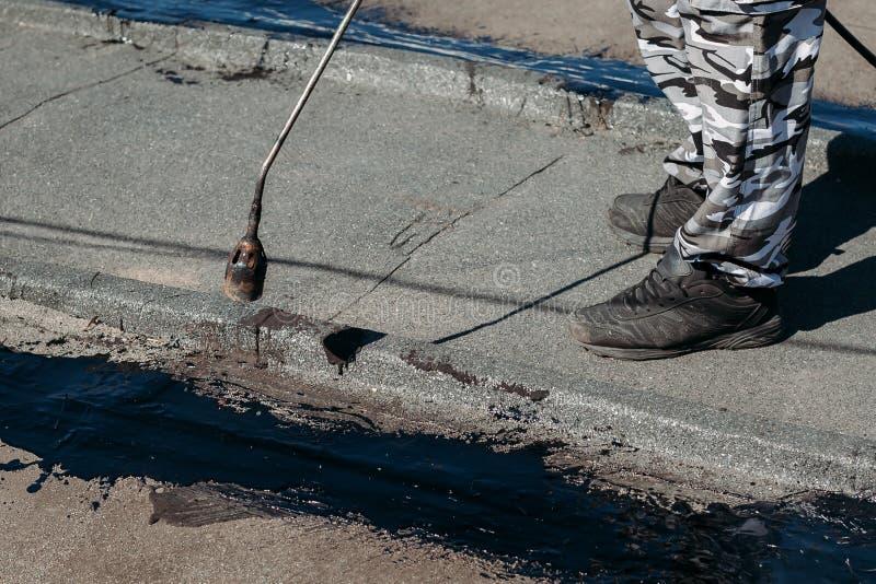 Arbeider die teerfolie installeren op het dak van de bouw Waterdicht systeem door gas en brand torching De teer van de dakreparat royalty-vrije stock fotografie