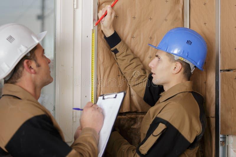 Arbeider die thermische isolatie installeren bij de bouw stock foto