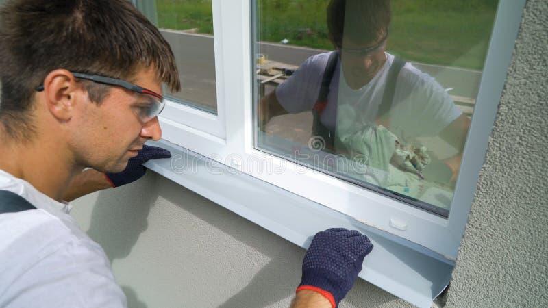 Arbeider die in veiligheidsbril en beschermende handschoenen metaalvensterbank installeren op extern pvc-raamkozijn stock fotografie